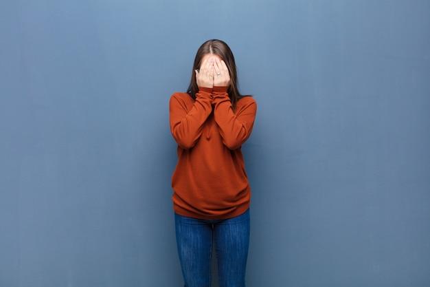 手で顔を覆い、驚いた表情で指の間をのぞき、横を向く
