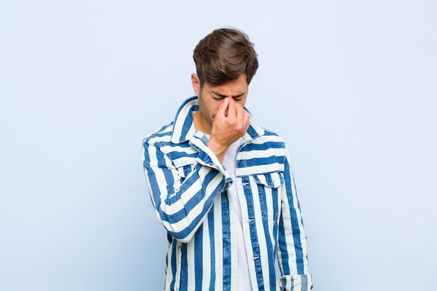 ストレスを感じ、不幸でイライラし、額に触れ、激しい頭痛の片頭痛に苦しむ
