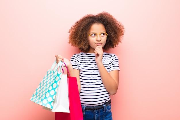 Афро-американская маленькая девочка против плоской стены с сумками