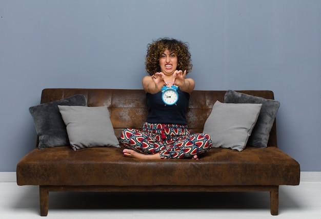 Молодая милая женщина дома сидя на софе с часами