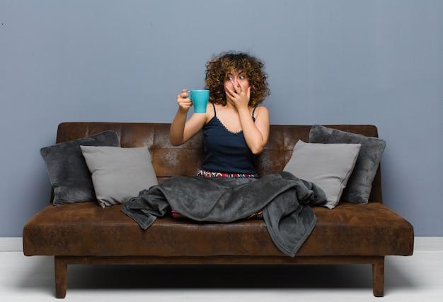 Молодая красивая женщина, имея кружку кофе, сидя на диване