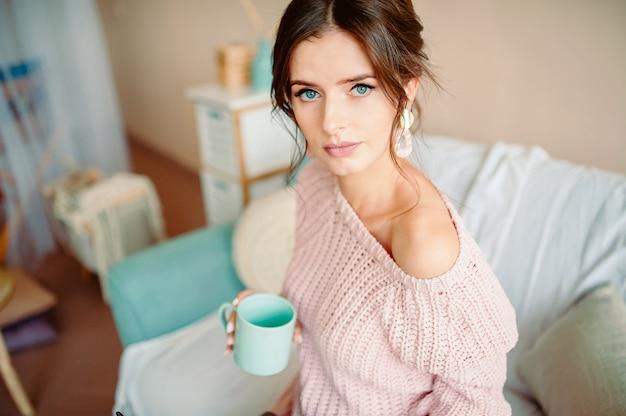 若い女性自宅で座って、コーヒーを飲みながら彼女のリビングルームでリラックス