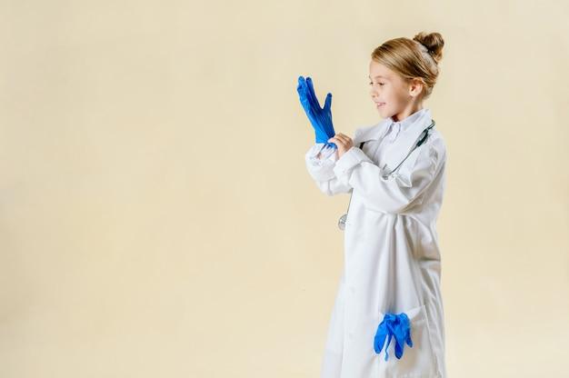 分離した聴診器で医者として服を着た愛らしい笑顔少女