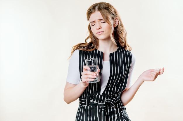 タブレットと水のガラスでひどい頭痛で金髪の女性のクローズアップ