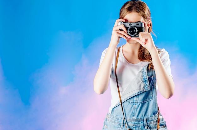 Молодая красивая женщина с ретро камерой собирается путешествовать