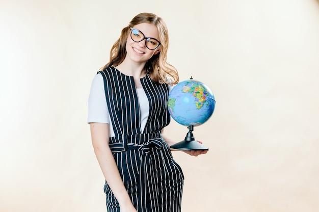Портрет мечтательной молодой бизнес-леди, держащей земной шар