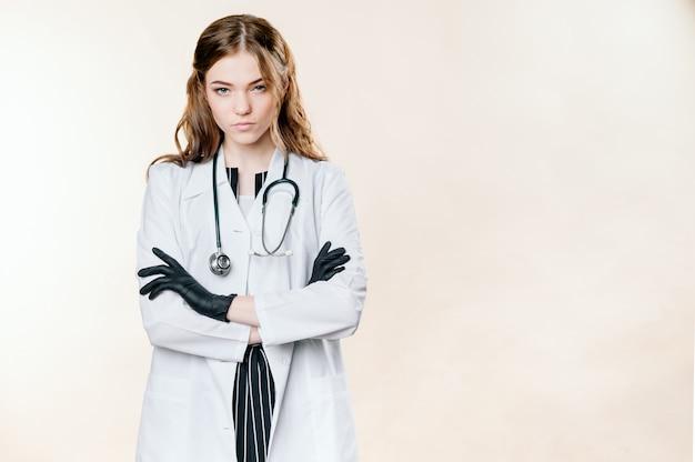 Девушка в костюме доктора на светлой однотонной стене