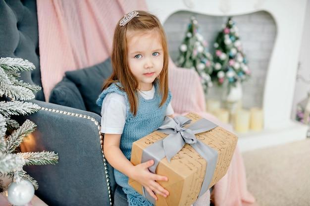 暖炉の横にあるおもちゃでクリスマスツリーの近くの小さな女の子