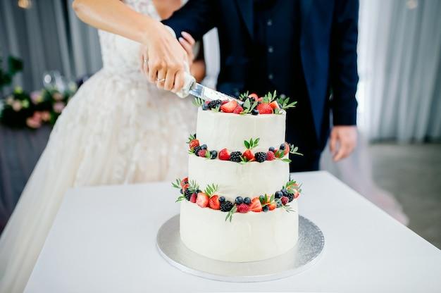 Свадебная церемония. руками молодоженов нарезать белый трехъярусный торт с клубникой и ежевикой