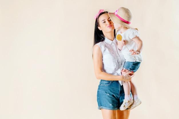 キスをする少し元気な幸せな娘のクローズアップの魅力的な顔は、愛情深い母親を抱擁します。