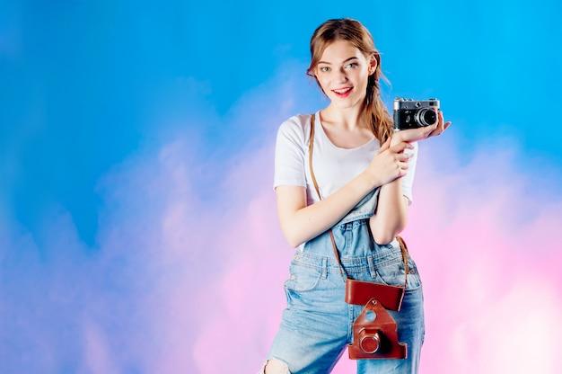 休暇に行く青色の背景にカメラでスーツケースの女の子