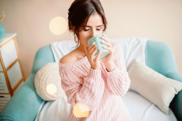 Молодая женщина дома сидит на современном стуле перед окном, отдыхая в своей гостиной, читает книгу и пьет кофе или чай
