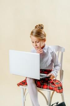 Маленькая девочка школьного возраста смотрит в ноутбук на светлом фоне, интернет-зависимость