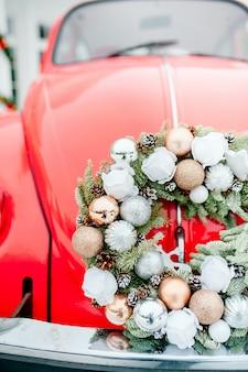 屋根の上のクリスマスプレゼントと花輪と雪の中で赤い車。お正月の雑用。