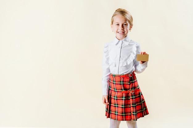 Маленькая белокурая девушка держа пустую карточку в школьной форме