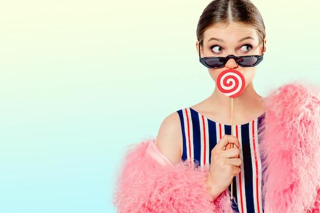 手に丸いロリポップのピンクの毛皮のコートサングラスの若い女性の肖像画。キャンディーで口を覆い、目をそらす