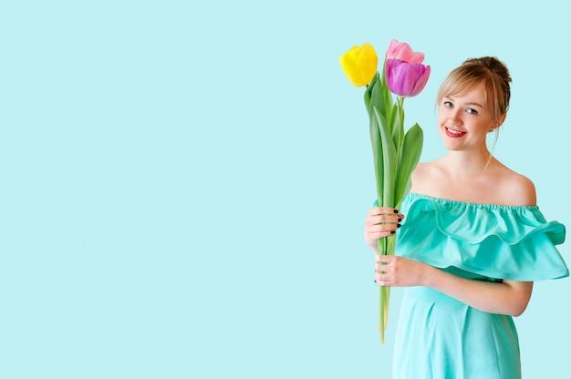 ポーズの大きなチューリップの花束を保持しているドレスを着た美しい若い女性の肖像画