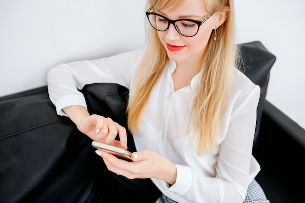 灰色の背景の上にスマートフォンを使用して笑顔の実業家。青いシャツとメガネを着ています。