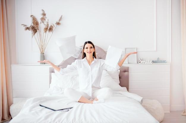 Бизнес, офис, победа, достижения и концепция образования - женщина, сидя на кровати бросил документы, радуется завершению работы
