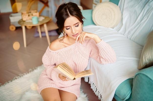 Рождество, комфорт, отдых и люди концепции - крупным планом счастливой молодой женщины, чтение книги дома над снегом
