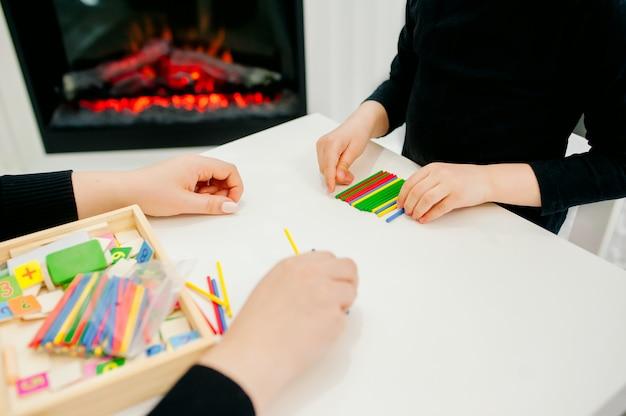 Мама играет с дочерью за столом с разноцветными деревянными палочками, готовится к школьным играм, учится партитуре