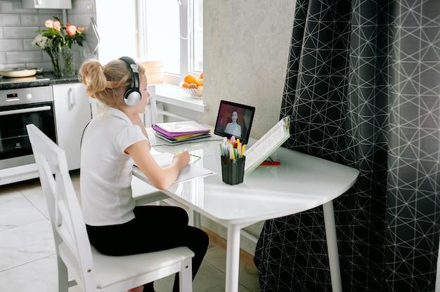 Подросток школьница носит наушники конференц-связи обучения онлайн с удаленным репетитором из дома. подростковая студент с помощью ноутбука, говорить в веб-камеру видео-чат, обучение урок с дистанционным учителем.
