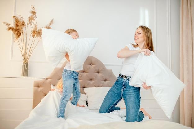 幸せな若い家族美しい母と娘がベッドと枕で遊ぶ、一緒に時間を過ごす