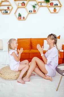 幸せなヨーロッパのお母さんが途中で座って、家でかわいい小さな娘と遊ぶ、小さな女の子と楽しいゲームをする