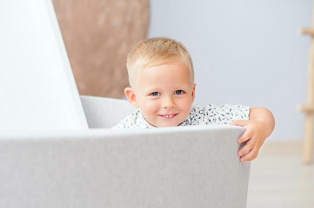 家で笑っているかわいい男の子。ブロンドの髪を持つヨーロッパの外観は、幸せそうな顔で見えます。