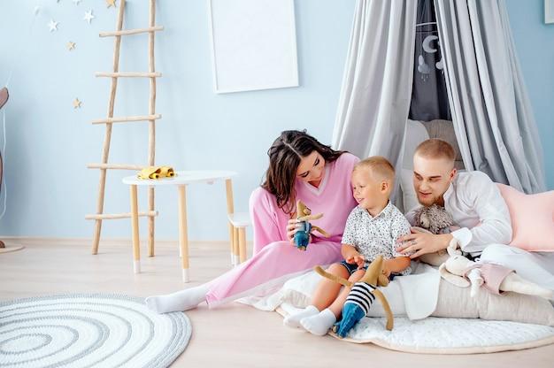 Семья мать отец и маленький сын играют вместе в детской игровой комнате