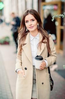 通りを歩いている美しいブルネットの少女の肖像画。持ち帰り用の使い捨て食器を片手で持ってください。笑顔。都市の都市のシーン。暖かい晴れた秋の天気。路上で