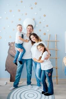 幸せな家族のお母さんお父さん娘息子の保育園で笑顔でお互いをハグ