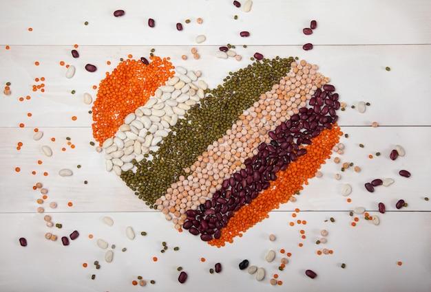 豆、レンズ豆、豆は白い木製の背景にハートの形で広げて