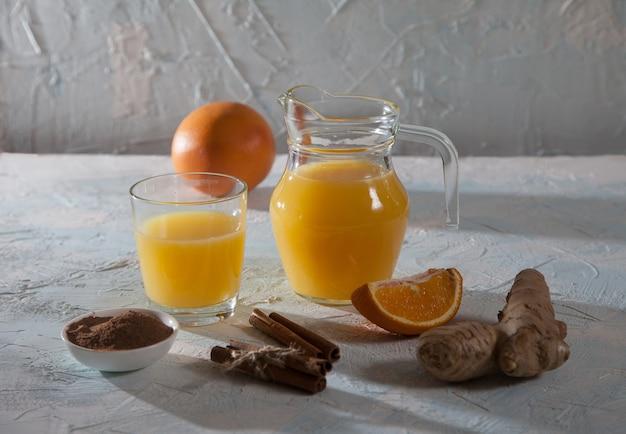 Апельсиновый сок с имбирем в стеклянном кувшине и в стакане, палочки корицы на светлом фоне. здоровье.