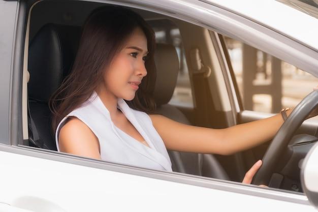 若い女性が車を運転します。
