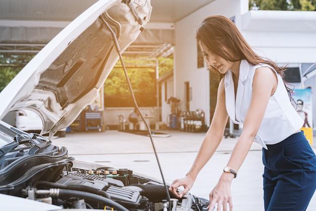車が壊れているアジアの女性。ボンネットを開き、エンジンを確認します。
