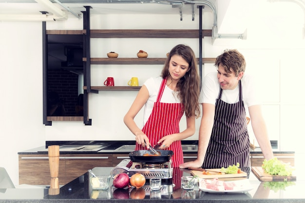 カップルは彼らの台所で料理をしています。
