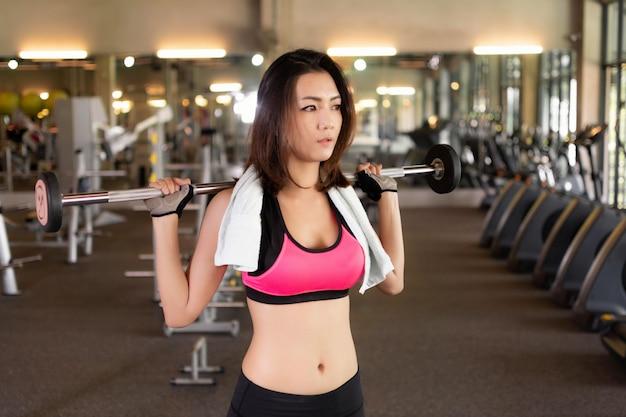 アジアの女の子はジムで運動しています。