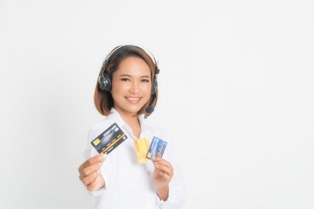 ヘッドセットの持株とクレジットカードを持つ女性のコールセンター。