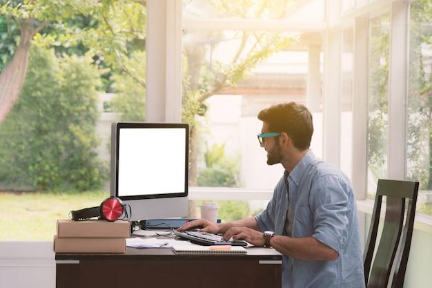 コンピューターでの作業に座っている男。