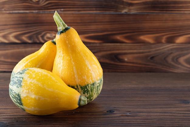 美しい自然な木製の背景に美しく、明るい野菜カボチャの黄色と緑。
