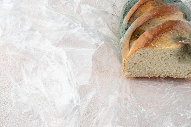 Плесень на хлебе несвежая буханка с большим покрытием плесени на фоне текстуры бумаги