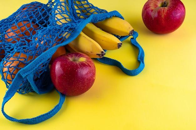 Синяя сумка-стринг с бананами, красными яблоками и мандаринами