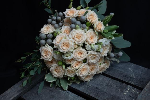 Красивый свадебный букет из кустистой кремовой розы, эвкалипта, брунея, питтоспорума и лизиантуса на черной стене.