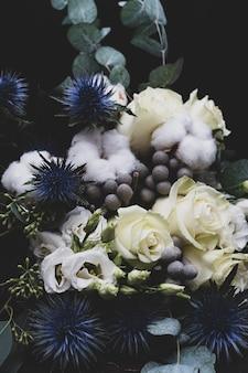 黒地に白いバラ、綿、エルギウムの冬のウェディングブーケ。花嫁のブーケ。