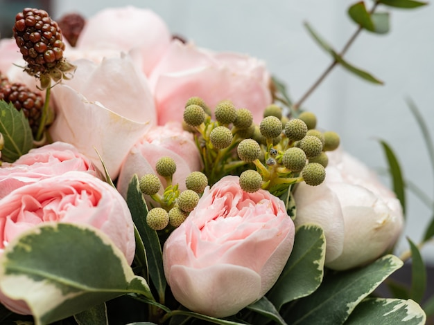 低木と牡丹の優しいピンクのバラの美しいウェディングブーケ。