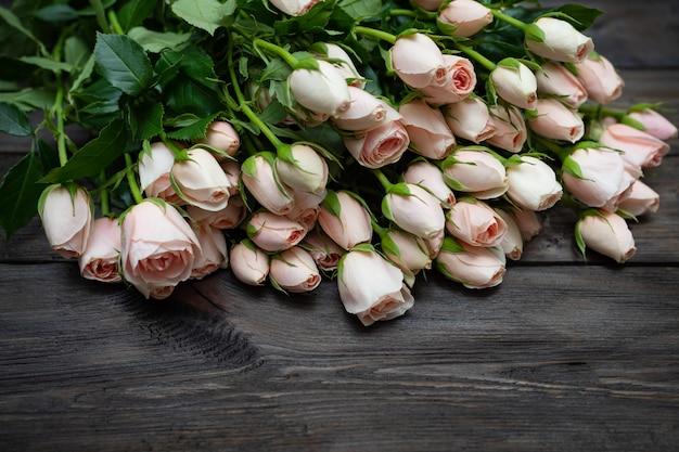 Розы, кустовые розы на темном деревянном столе.