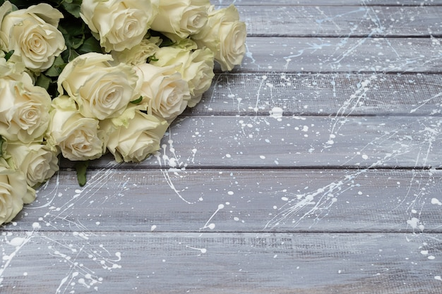 Белые розы на сером фоне деревянных. копировать пространство