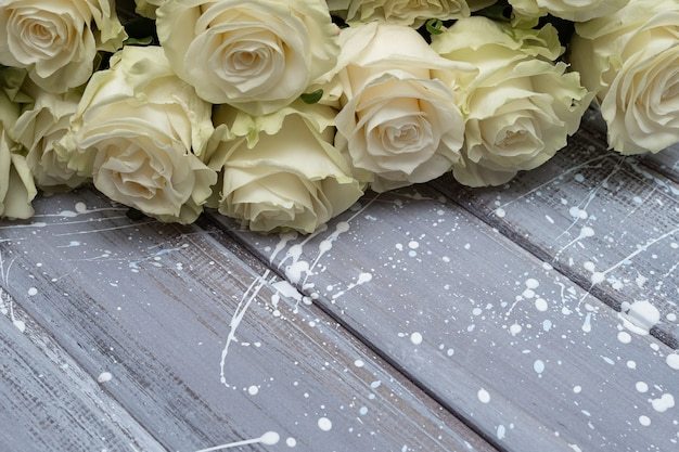 灰色の木製の背景に白いバラ。コピースペース。