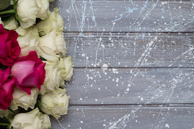 灰色とピンクの背景に白いバラ。